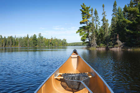 piragua: Canoa amarilla con red de pesca en un lago del norte de Minnesota con pinos Foto de archivo