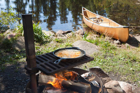fish fire: Fish cooking in a frying pan over an open fire with a canoe and northern Minnesota lake in the background