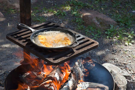 fish fire: Shore lunch of frying fish in a cast iron pan on an outdoor grill