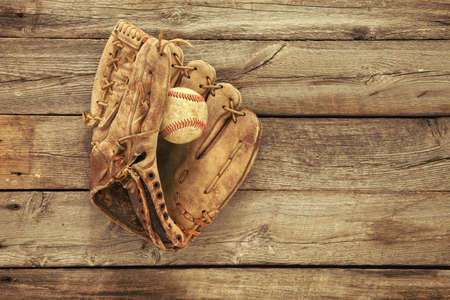 mitt: Vintage baseball mitt and ball on grungy, rough wood background viewed from above