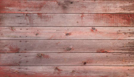 An old red and gray wooden barn door with some nails