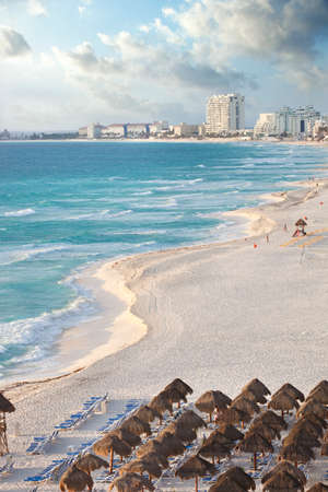 curving: View along a curving beach of the brilliant blue ocean and distant hotels in Cancun, Mexico