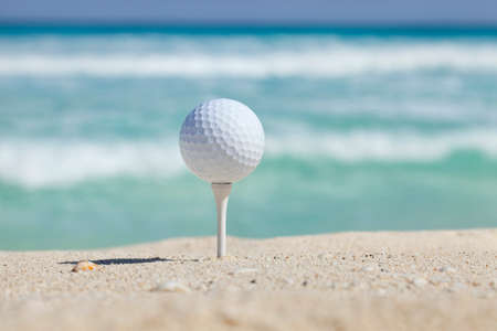 White golf ball on tee in sand of beach with soft focus ocean waves behind Фото со стока
