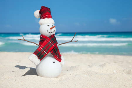 scarf beach: Miniature snowman wearing hat and scarf on the beach with the blue caribbean behind Stock Photo