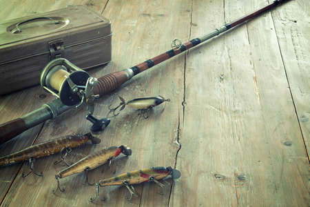 Antique tackle box, bait-casting fishing rod, and lures on a grunge wood surface Standard-Bild