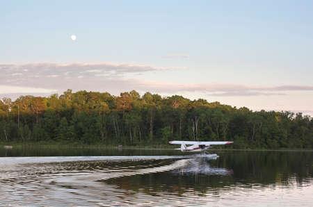 A small floatplane taxis for takeoff on a calm Minnesota lake at sundown