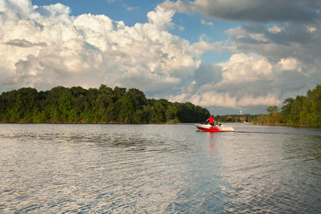 speedboat: Speedboat heads out onto a Minnesota lake in evening sunlight below dramatic clouds