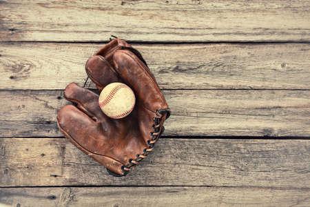 mitt: Vintage leather baseball mitt and ball on grunge wood background