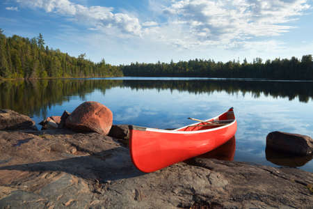 A red canoe rests on a rocky shore of a calm blue lake in the Boundary Waters of Minnesota 스톡 콘텐츠