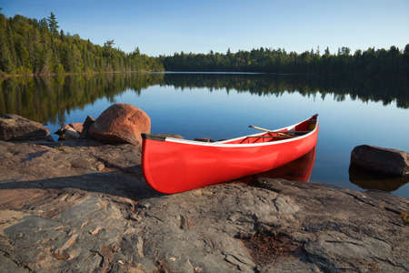 waters: A red canoe rests on a rocky shore of a calm blue lake in the Boundary Waters of Minnesota Stock Photo