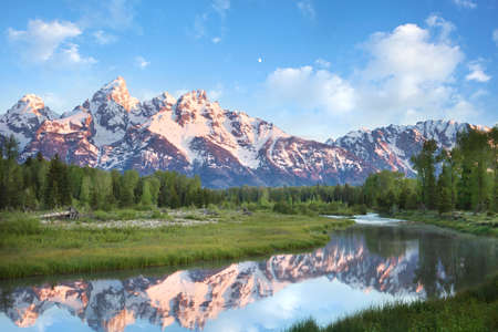 grandeur: The magnificent Grand Teton mountains reflected in the Snake River at dawn