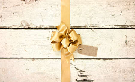 A gold Christmas bow and ribbon with a tag on a rosy white distressed wood background Stock Photo