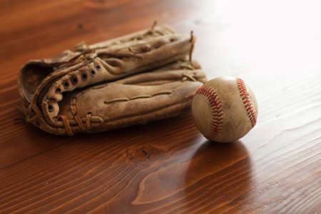 mitt: A selective focus view of a vintage baseball and mitt on pine wood background Stock Photo