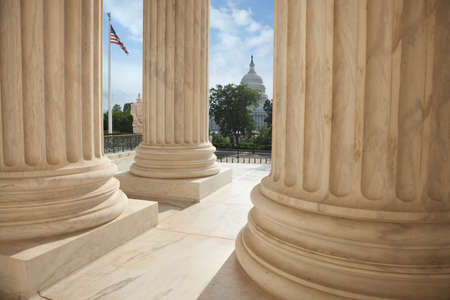 supreme court: Close up of the columns  of the Supreme Court building with an American flag and the US Capitol in the background Stock Photo