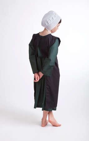 Una joven Amish descalza en un traje verde y negro aislado en un fondo Foto de archivo - 69742017