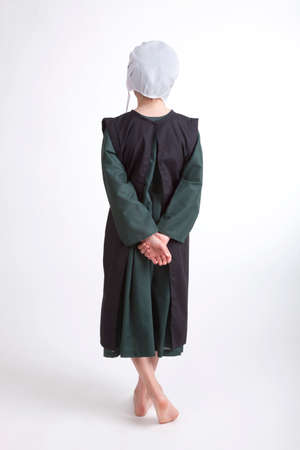 amish: A young barefoot Amish girl in a green and black outfit isolated on a background
