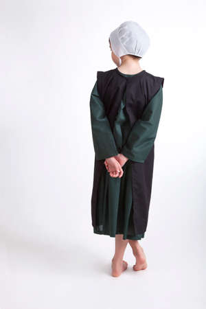 A young barefoot Amish girl in a green and black outfit isolated on a background