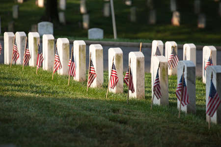 Selective focus view of marble grave markers with flags at Arlington National Cemetery on Memorial Day