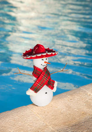 A miniature snowman with a red scarf and sombrero by the edge of a pool in Cancun, Mexico Stock Photo