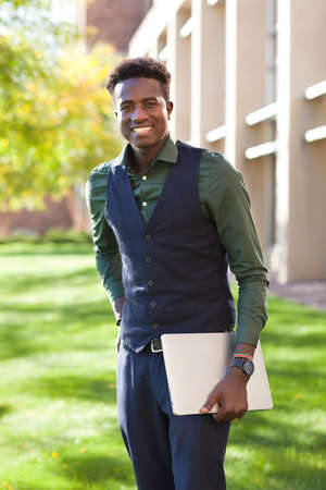 Handsome young black student man smiles standing on colege campus with his computer Stock Photo