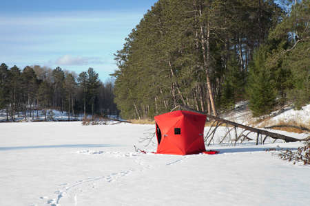 A red portable ice fishing shelter on a remote Minnesota lake on a sunny afternoon Stock Photo