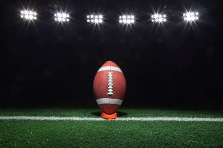A football on a tee on a yard line under lights at night 写真素材 - 103954817