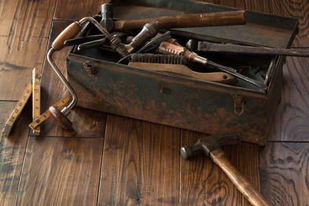 Antique tools and grungy toolbox on dark wood surface Stockfoto