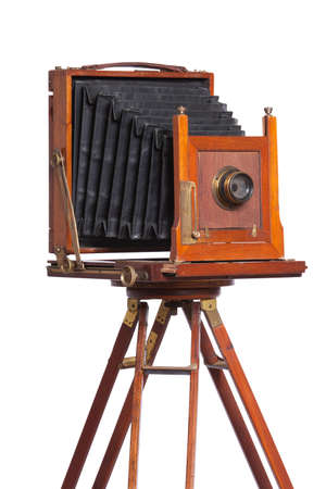 An antique bellows camera atop an old wooden tripod isolated on white