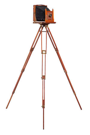 An antique wood camera with bellows atop an old wooden tripod isolated on white