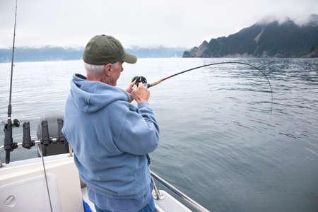 A senior fisherman fights a fish in the ocean near Seward, Alaska Stockfoto