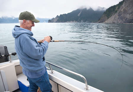 Smiling senior fisherman reels in a salmon in the ocean near Seward, Alaska