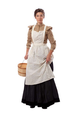 Young prairie woman with apron holding skirt and a basket isolated on white background Stock Photo