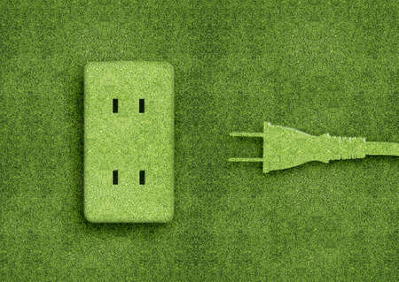 green power: Green energy concept, Green power cord in electric outlet on a green grassland.