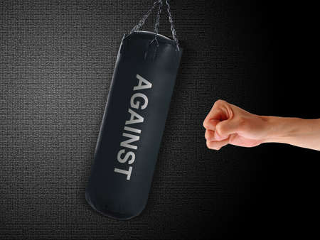 enemy: boxing punch bag and hand punching it on black background