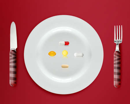 cutlery and plate with pills and capsules on red background. photo