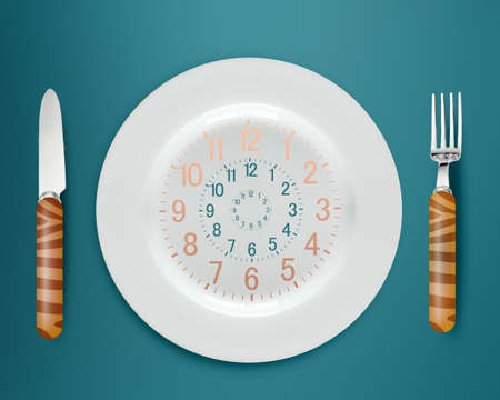 intake: Lunch time concept, clock in plate, knife and fork
