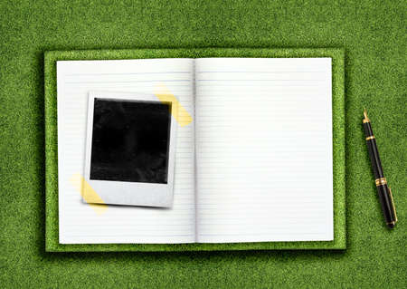 Biography,curriculum vitae concept, blank opened book and empty photo on the green grassland and pen photo