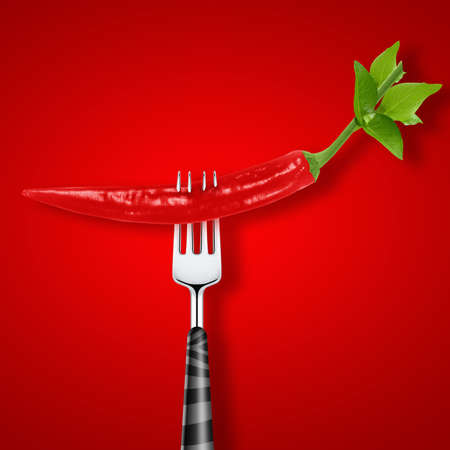 red hot chili pepper pierced by fork on red background .