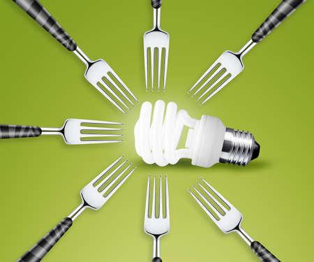 Forks around light bulb, on green background  photo