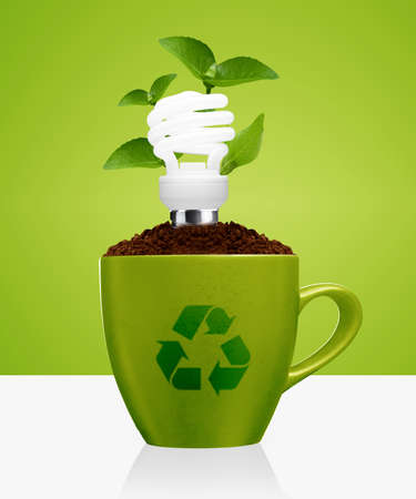 energy supply: modern energy-saving concept,  bright bulb, green mug, green leaves and recycle sign. Stock Photo