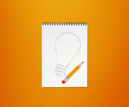 pencils and notepad and drawing light bulb on orange background. photo