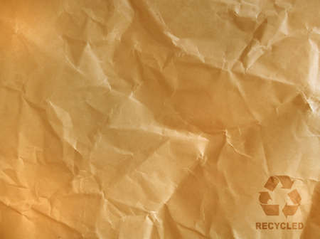 crimped: recycle sign on brown crumpled paper. Stock Photo