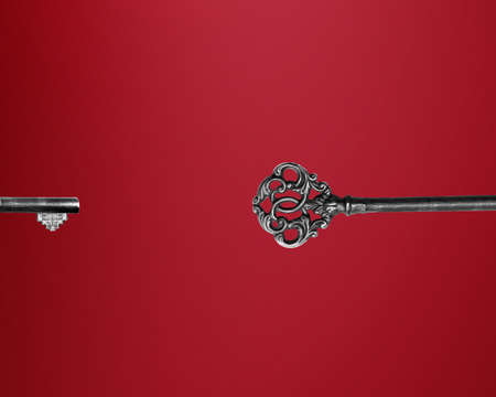 Old key on red background, conceptual image for solutions photo