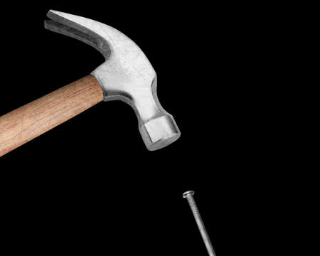 construction nails: Hammer hitting a nail on black background. Stock Photo