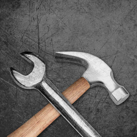 spanner and hammer on Scratched metal background. photo