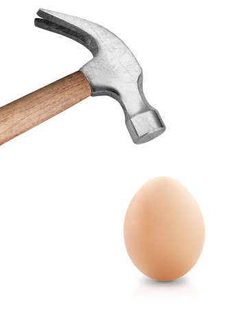 Hammer hitting an egg . Stock Photo
