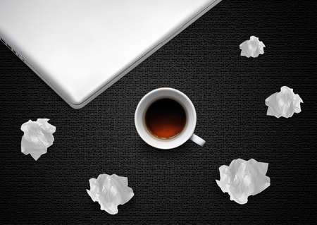 Crumpled colorful papers with laptop and coffee on black desktop.