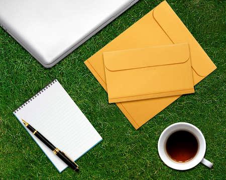 envelops: business desktop with laptop, notepad, envelops and coffee on grassland.