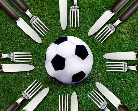 catchy: Football sport, soccer ball on grassland and knife and fork around.