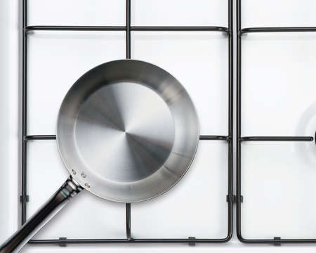 Empty steel frying pan on stove photo